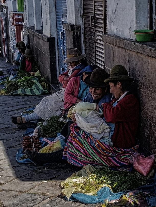 Peruvian women selling herbs with baby on the hands